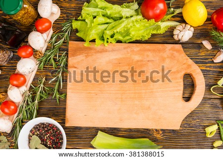 Delicious tomatoes, mushrooms, green leaf lettuce, lemon, garlic and other vegetables surrounding empty cutting board with copy space
