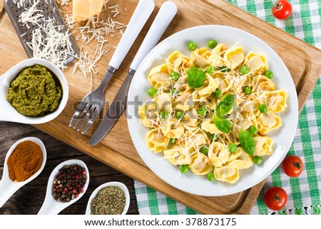 Delicious tortellini with green peas, fried Pine nuts, decorated with basil leaves on a white dish with spice, sauce pesto and parmesan cheese on an old rustic table, italian style. close-up, top view - stock photo
