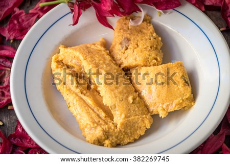 Delicious traditional Cuban tamal or tamales made from corn,  ready to eat, served fresh and hot on top of a white plate - stock photo