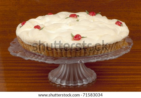 Delicious traditional homemade lemon ,meringue pie on an elegant glass cake stand, decorated with red cherries and green angelica. - stock photo