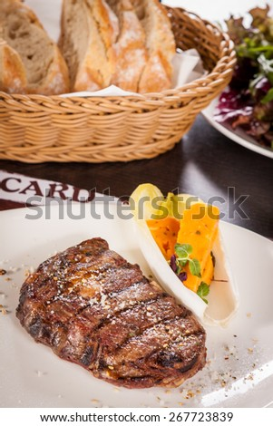 Delicious trimmed lean portion of thick grilled beef steak with seasoning served on a white plate, close up with shallow dof - stock photo