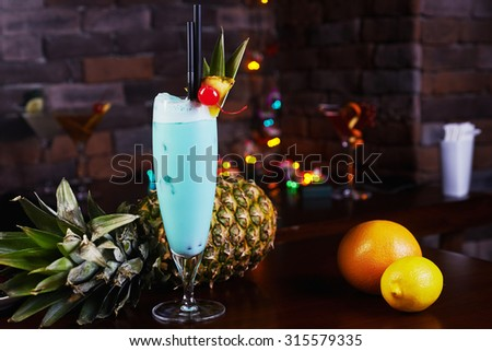 Delicious tropical blue curacao alcoholic cocktail garnished with a fresh pineapple slice and maraschino cherries on a table in the restaurant with background of beautiful disco lights. soft focus - stock photo