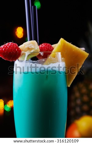 Delicious tropical blue curacao alcoholic cocktail garnished with a fresh pineapple slice and berries on a table in the restaurant with bright backgrounds of beautiful disco lights. soft focus - stock photo