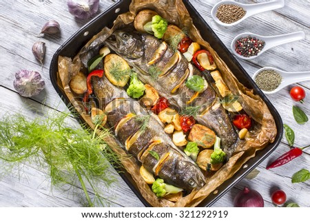 delicious trout fishes baked with potatoes, broccoli, lemon, tomatoes and spices in baking dish on a wooden background, view from above - stock photo
