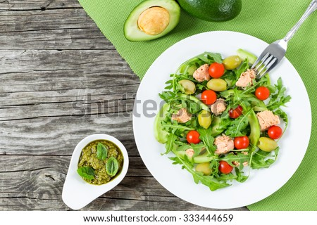 delicious tuna salad with arugula, green olives, avocado and cherry tomatoes  with sauce pesto in the gravy boat, horizontal top view - stock photo