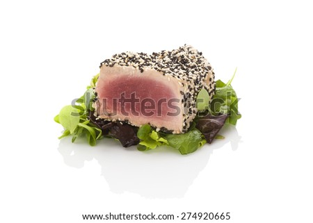 Delicious tuna steak on green salad isolated on white background. Culinary seafood eating. - stock photo
