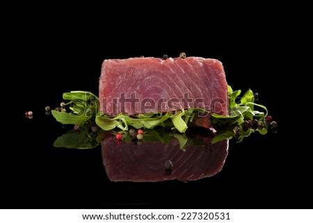 Delicious tuna steak with salad and colorful peppercorns. Raw tuna steak, sashimi sushi. - stock photo