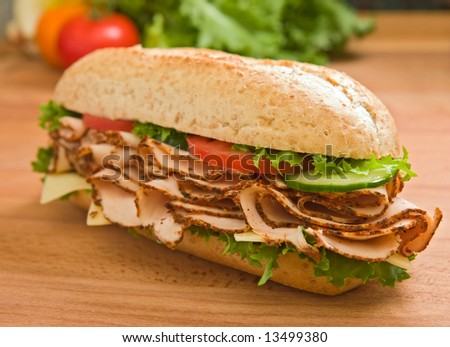 Delicious turkey breast / chicken breast  sandwich with lettuce, cheese, tomatoes and cucumbers