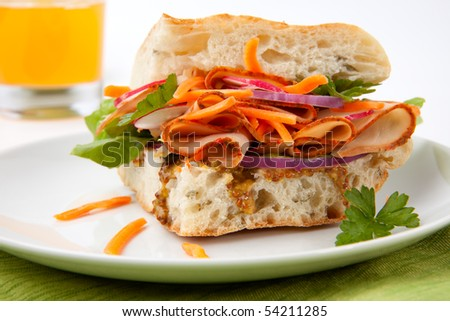 Delicious Turkey Breast Sandwich - rosemary ciabatta bread, turkey breast, whole grain mustard dressing, carrots, radish, red onion and parsley.