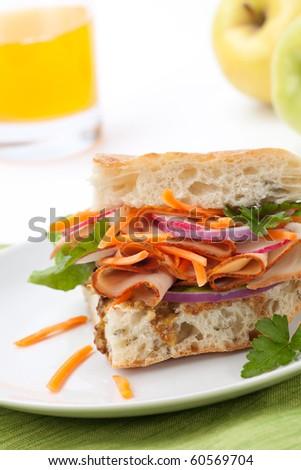 Delicious Turkey Breast Sandwich - rosemary ciabatta bread, turkey breast, whole grain mustard dressing, carrots, radish, red onion and parsley. - stock photo