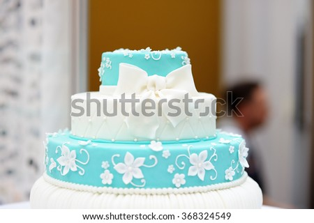Delicious turquoise wedding cake decorated with sugar flowers  - stock photo