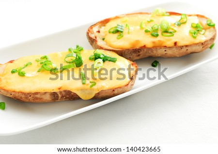 delicious twice baked potatoes smothered with aged cheddar cheese - stock photo