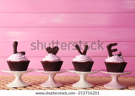 Delicious Valentine Day cupcakes on pink wooden background - stock photo