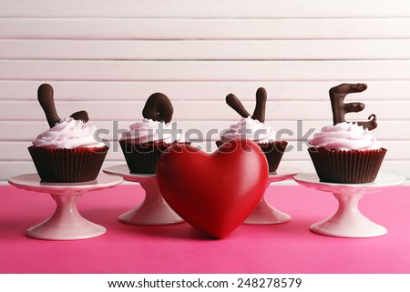 Delicious Valentine Day cupcakes on wooden background - stock photo