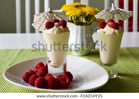 Delicious vanilla mousses topped with raspberry fruit on white wooden table