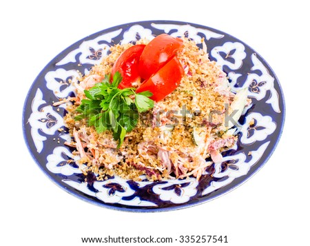 Delicious veal salad with fresh vegetables covered with grated walnuts on authentic oriental plate. Isolated on a white background. - stock photo