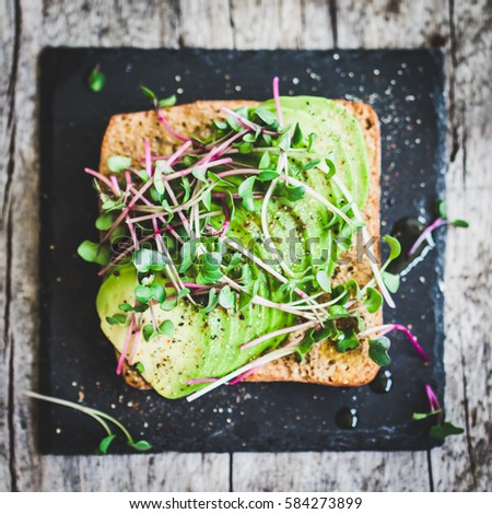 delicious vegan sandwich with avocado and cress radish, top view.
