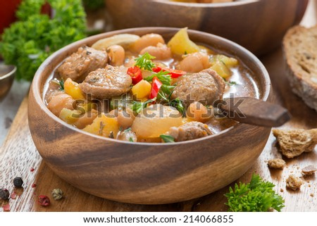 delicious vegetable stew with sausages in a wooden bowl, close-up - stock photo