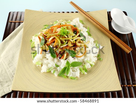 Delicious vegetarian asian stir fry on boiled white rice with thai basil and vietnamese mint. - stock photo