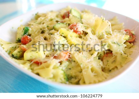 Delicious vegetarian bowtie pasta with zucchini, squash, tomatoes, and cheese. - stock photo