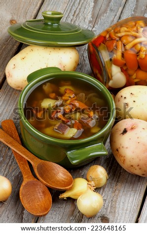 Delicious Vegetarian Chanterelle Mushrooms Soup in Green Pot with Raw Potato, Onion, Marinated Mushrooms and Wooden Spoons on Rustic Wooden background