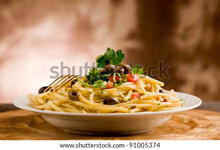 delicious vegetarian dish of pasta with olives and parsley on wooden table - stock photo