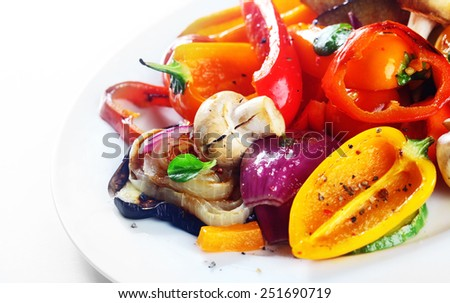 Delicious vegetarian meal or grilled or roast vegetables with sweet pepper, mushrooms, onions and herbs serve on a white plate - stock photo