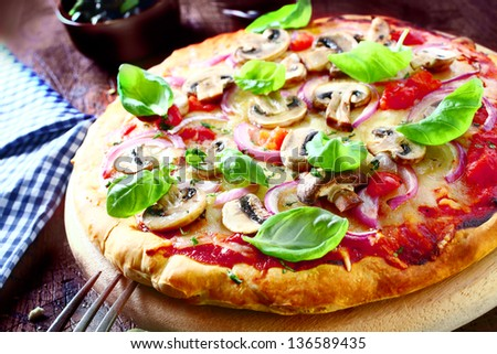 Delicious vegetarian pizza topped with tomato, melted cheese, mushrooms, onions and fresh basil leaves served on a wooden board, high angle view. More pizza at my port. - stock photo