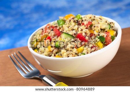 Delicious vegetarian quinoa salad with bell pepper, cucumber and tomatoes (Selective Focus, Focus one third into the bowl) - stock photo