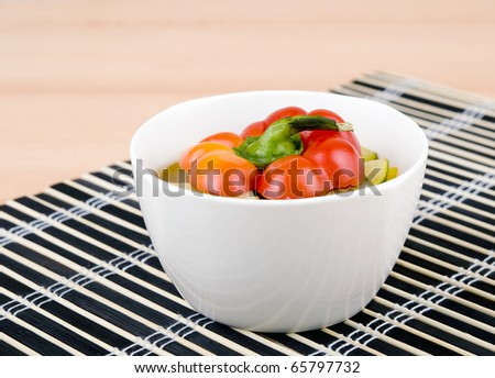 Delicious vegetarian soup made from zucchini and yellow paprika served in white porcelain bowl on black bamboo mat