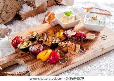 Delicious vegetarian winter barbecue with assorted vegetables and tofu or bean curd on skewers and grilled corn on the cob served on a wooden board outdoors in winter snow - stock photo