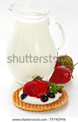 Delicious waffle with berries and jug of milk.