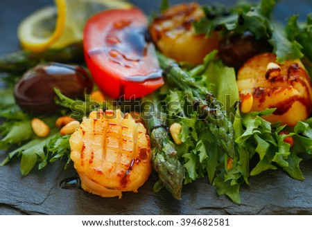 Delicious warm salad of lettuce, asparagus, scallops with olives, tomatoes, lemon, pine nuts and balsamic vinegar. Shallow depth of field - stock photo