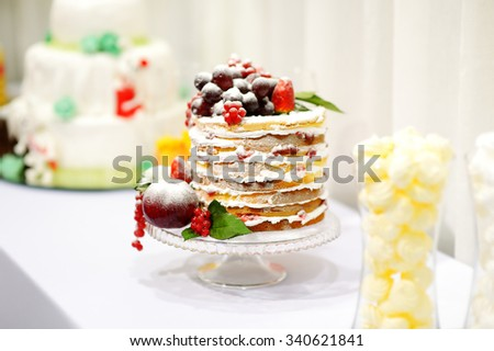 Delicious wedding cake decorated with fruits - stock photo