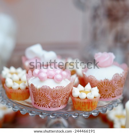 Delicious wedding cupcakes on glass dish - stock photo