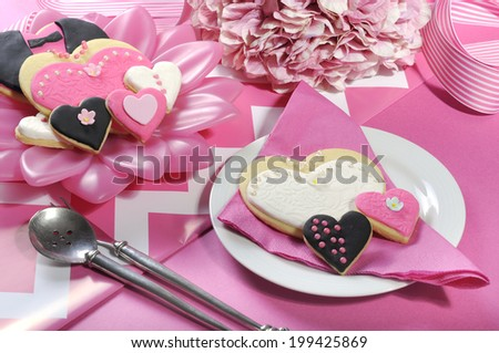 Delicious wedding party bride and groom pink, white and black heart shape biscuit cookies bridal table favors on a pink and white decorated reception table. - stock photo