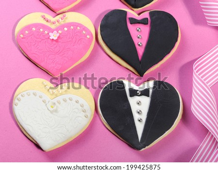 Delicious wedding party bride and groom with bridesmaid and groomsmen pink, white and black heart shape biscuit cookies bridal table favors, close up. - stock photo
