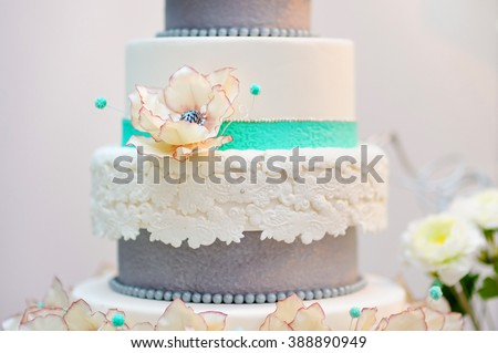 Delicious white and grey wedding or birthday cake decorated with flowers - stock photo