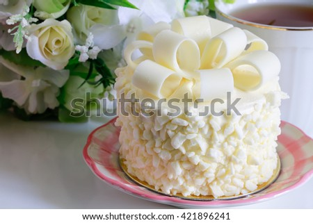 Delicious white cake and a beautiful flowers cup of herbal tea with flowers - stock photo