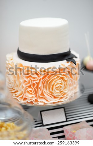 Delicious white wedding cake decorated with cream roses - stock photo
