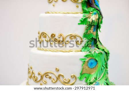 Delicious white wedding cake decorated with gold and green tracery  - stock photo