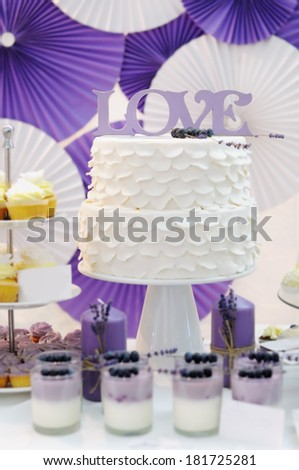 "Delicious white wedding cake decorated with word ""love"" - stock photo"
