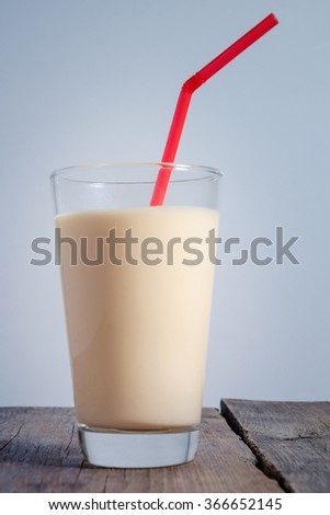 delicious yogurt in a glass on a wooden background in a village
