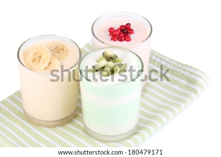 Delicious yogurt with fruits tastes in glasses on napkin, isolated on white