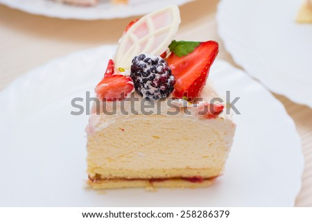 Delicious yummy beautiful appetizing strawberry blackberry mascarpone cream cake with mint leaves and white chocolate - stock photo