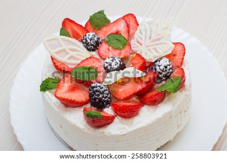 Delicious yummy beautiful appetizing strawberry blackberry mascarpone cream cake with mint leaves and white chocolate