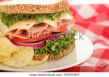 Deliciously fresh ham and cheese sandwich with crisp potato chips - stock photo
