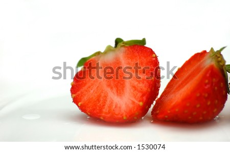 Deliciously red strawberry cut into half(on white plate) - stock photo