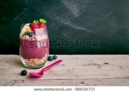 Deliciously sweet acai fruit dessert with pieces of banana, strawberry and blueberry with oats next to spoon on wooden table with copy space - stock photo