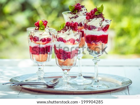 Delicous redcurrant sundaes or desserts served outdoors on at tray with tall glasses of colorful layered berry coulis, ice cream or frozen yoghurt, cream and ripe red redcurrants on a cake base - stock photo